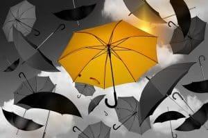 Yellow Umbrella Amidst Black Umbrellas