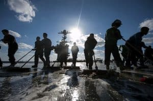 sailors cleaning the deck as a team