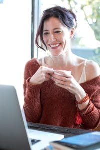 smiling woman in front of laptop
