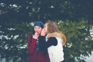 girls whispering winter clothes