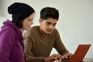 man and woman in front of laptop