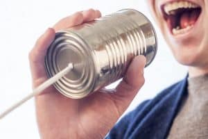 man speaking into a makeshift tin can telephone