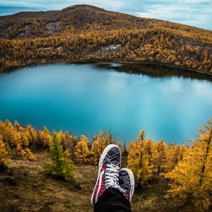sneakers in the foreground, lake in the background