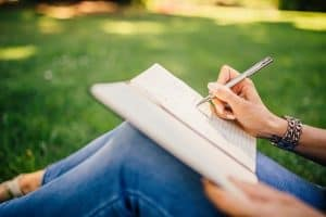writing in a notebook outdoors