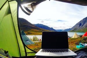 laptop in a tent on a campsite with a view of mountains and a lake