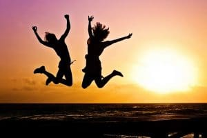 silhouette of two girls jumping on the beach with setting sun in the background