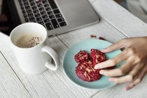 desk with a cup of coffee, a plate of cookies, and a laptop