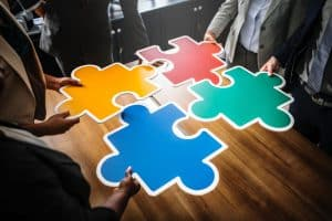 four giant pieces of a puzzle held by four people in an office
