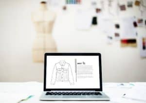 designing jacket on laptop with fashion elements in the background
