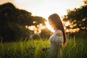 girl in a white dress standing in a field