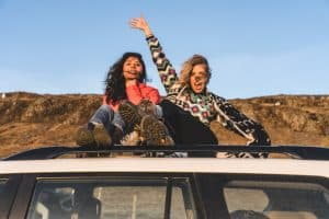 two girls on the roof of a car