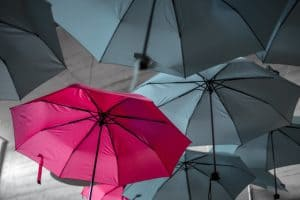 a single red umbrella among gray ones