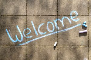 "the word ""welcome"" written in chalk on a sidewalk"