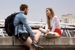 man and woman talking while sitting on bridge