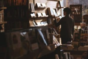 man browsing through books in a book store