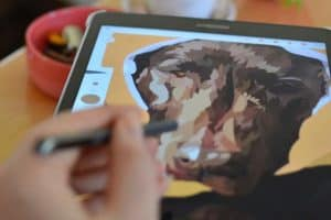 artist using stylus to draw a dog on a tablet