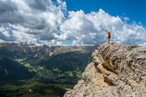 woman on top of mountain with clouds in the background