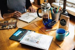 artist in coffee shop with various art materials and unfinished drawings on the table