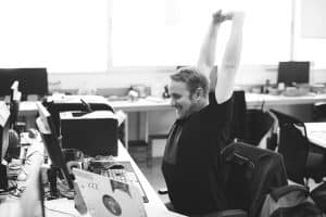 man stretching arms in front of workdesk