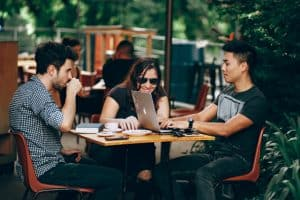 two men and a woman talking in an outdoor coffee shop