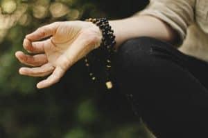 hand wearing mala beads
