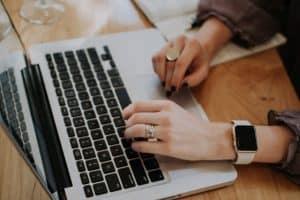 hands typing on macbook