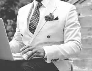 black and white photo of a man in white suit using a laptop