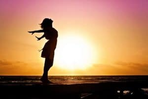 woman with outstretched arms backlit by the sunset