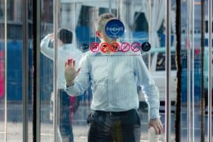 man coming in through a glass door