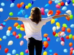woman with outstretched hands with balloons in the background