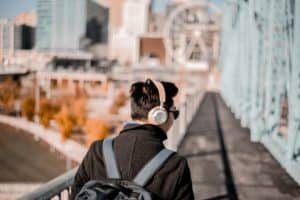 male listening using headphones while wearing a backpack and crossing a bridge
