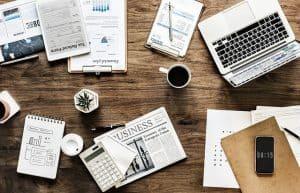 marketing materials, laptop, newspaper, charts, calculator