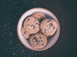 bowl of chocolate chip cookies set on coffee beans