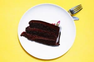 slice of chocolate cake on plate above fork and knife