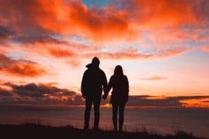 couple holding hands against the sunset