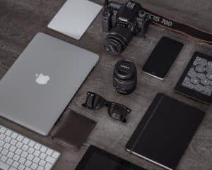 laptop, camera, smartphone, ereader, wallet, notebook on desk