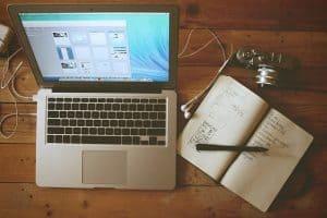 macbook beside a notebook and camera
