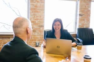 woman interviewing man in front of laptop