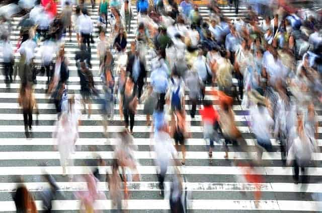 blurred photograph of people crossing a busy street
