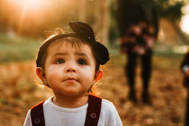 female preschooler looking up with light behind her