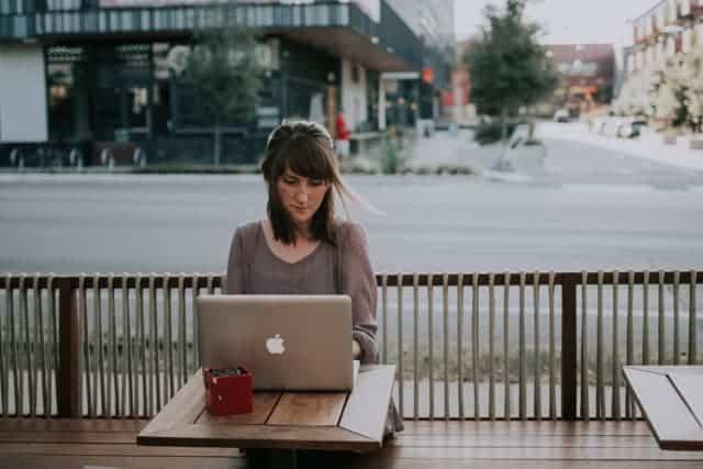 woman using laptop in an outdoors café