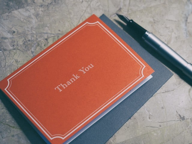 red thank you card with pen beside it