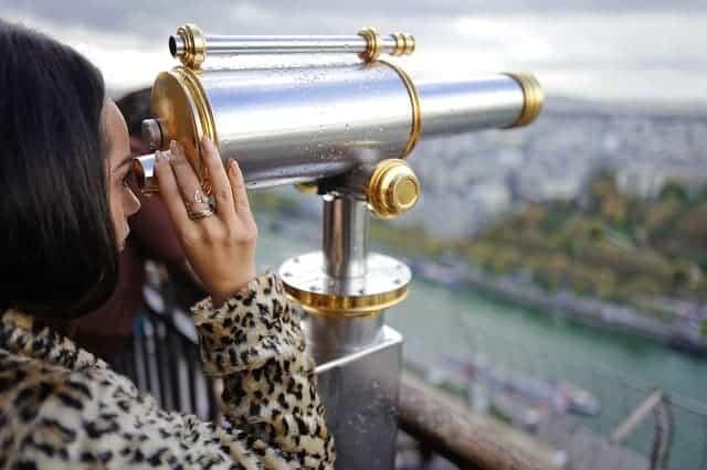 woman looking through big binoculars